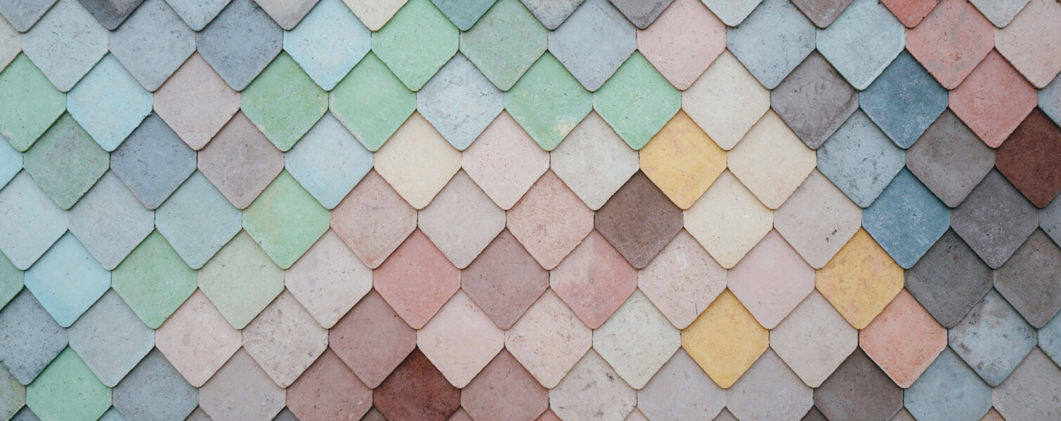 A multi coloured wall of diamond shape tiles